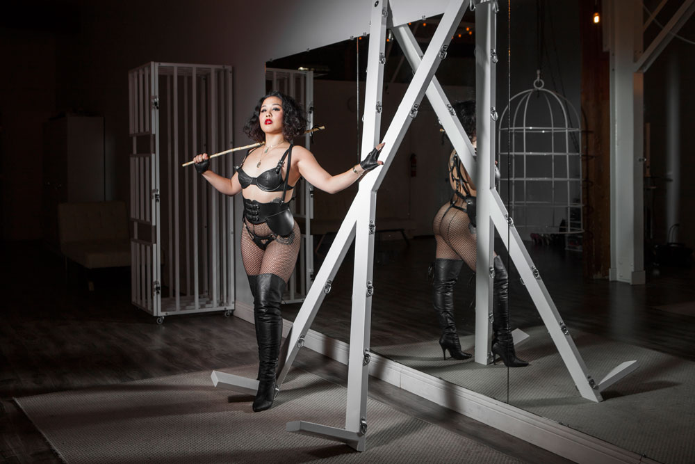 Leather Domina An Li with cane and leather outfit.
